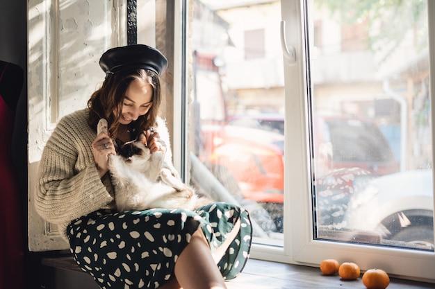Ładna kobieta trzyma jej kot łap łap rozciągać