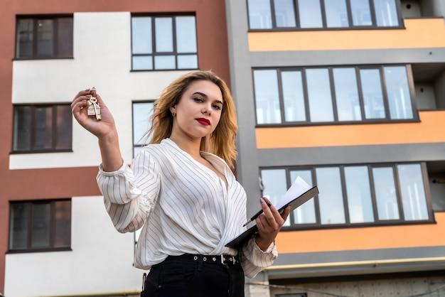 Ładna kobieta trzyma klucze do nowego domu. koncepcja sprzedaży