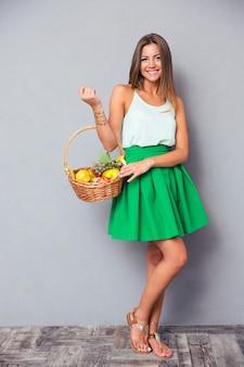 Ładna kobieta trzyma kosz z owocami