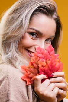 Ładna kobieta trzyma liście klonu patrzeje kamerę