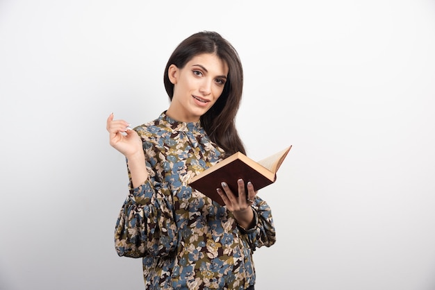 Ładna kobieta trzyma otwartą książkę.