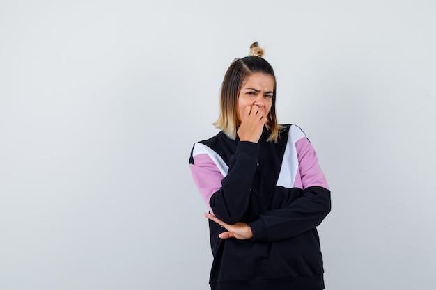 Ładna kobieta trzyma rękę na ustach w bluzie i wygląda na niezadowoloną