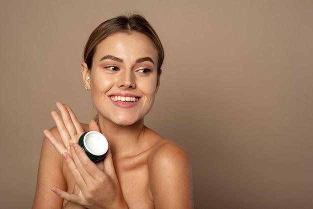Ładna kobieta trzyma słoik kremu nawilżającego w studio. koncepcja pielęgnacji i nawilżania skóry. portret pięknej kobiety, stosując krem do twarzy do pielęgnacji skóry.