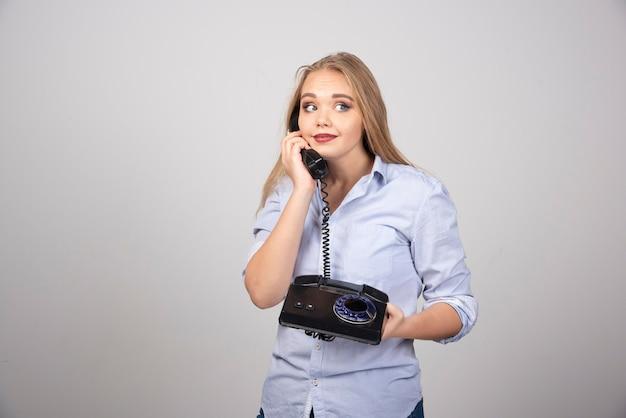 Ładna kobieta trzyma telefon i rozmawia na białym tle szarej ścianie.