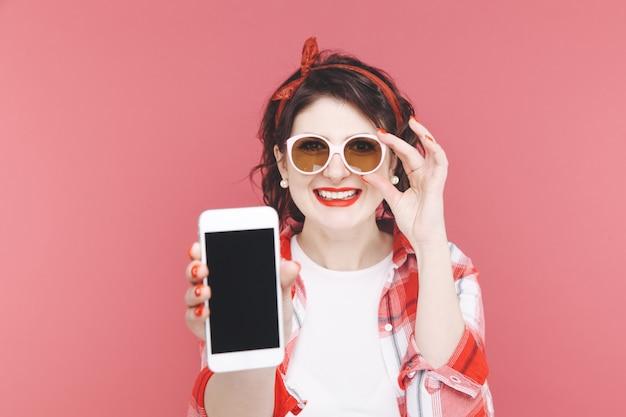 Ładna kobieta trzyma telefon i uśmiecha się w czerwonym studio.
