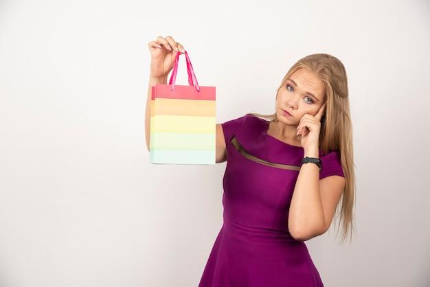 Ładna kobieta trzyma torbę na prezent i myśli.