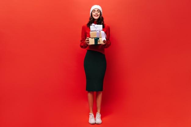 Ładna kobieta trzyma trzy pudełka na prezenty