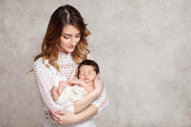 Ładna kobieta trzyma w ramionach noworodka. portret matki i małego dziecka. skopiuj miejsce na tekst
