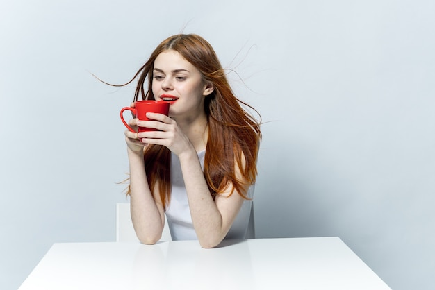Ładna kobieta trzyma w ręku czerwony kubek, siedząc przy stole do kawy