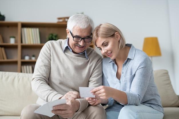Ładna kobieta trzyma zdjęcie swojej rodziny, pokazując je starszemu ojcu i omawiając je w domu
