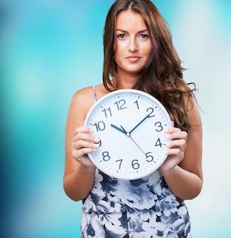 Ładna kobieta trzyma zegar