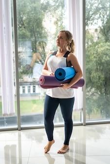 Ładna kobieta trzymając dywanik do jogi przed ćwiczeniami stojąc przed oknem na siłowni
