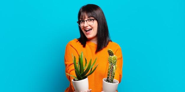 Ładna kobieta trzymająca doniczki z kaktusami
