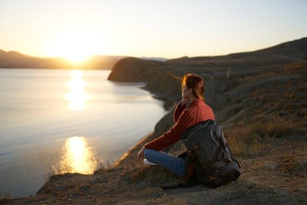 Ładna kobieta turystka z plecakiem podziwiająca krajobraz o zachodzie słońca wakacje