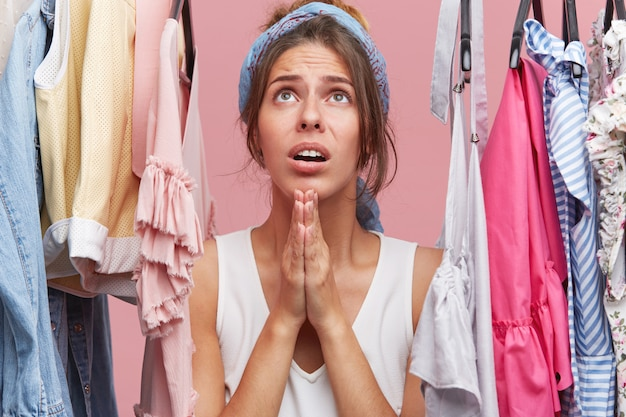 Ładna kobieta ubrana niedbale, stojąca wśród ubrań wiszących na wieszaku w swojej garderobie, trzymając się za ręce w modlitwie,