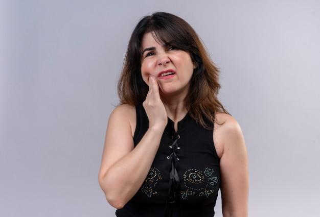 Ładna kobieta ubrana w czarną bluzkę cierpiących na ból zęba, trzymając policzek ręką