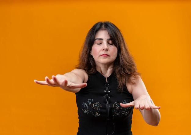 Ładna kobieta ubrana w czarną bluzkę jest zamykających oczy na pomarańczowym tle