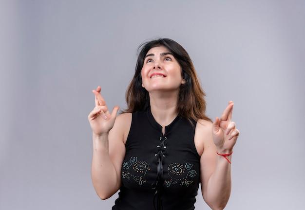 Ładna kobieta ubrana w czarną bluzkę patrząc z nadzieją, że krzyżują palce