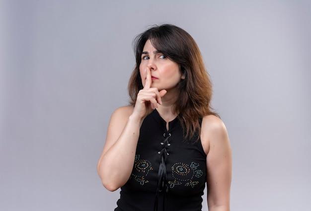 Ładna kobieta ubrana w czarną bluzkę poważnie robi znak ciszy palcem do myszy