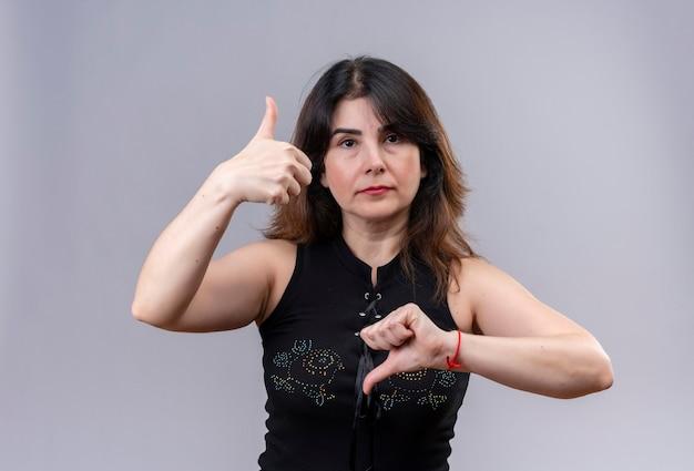 Ładna kobieta ubrana w czarną bluzkę robi szczęśliwy kciuk w górę i nieszczęśliwy kciuk w dół na szarym tle