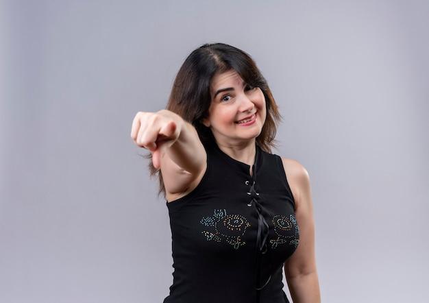 Ładna kobieta ubrana w czarną bluzkę szczęśliwie wskazując palcem wskazującym