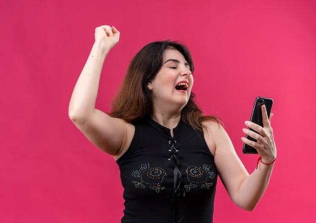 Ładna kobieta ubrana w czarną bluzkę wygląda radośnie na telefon