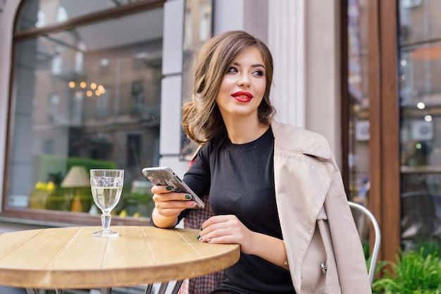 Ładna kobieta ubrana w czarną sukienkę i beżowy tren ze stylową fryzurą i czerwonymi ustami na tarasie