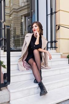 Ładna kobieta ubrana w czarną sukienkę i beżowy tren ze stylową fryzurą i czerwonymi ustami na ulicy