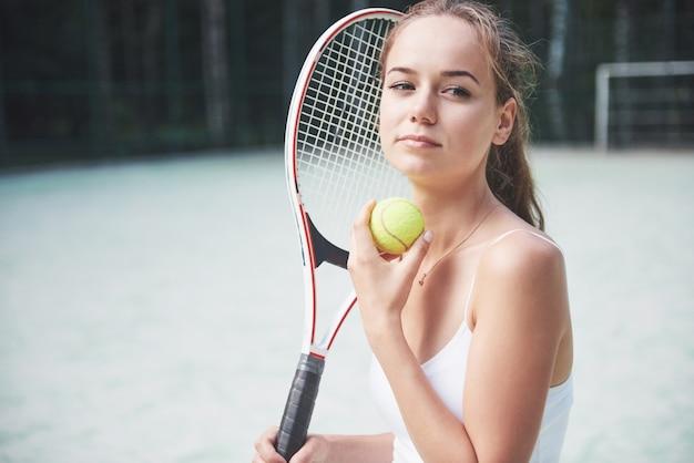 Ładna kobieta ubrana w sportowy kort tenisowy na korcie.