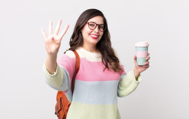 Ładna kobieta uśmiecha się i wygląda przyjaźnie, pokazując numer cztery. koncepcja studenta