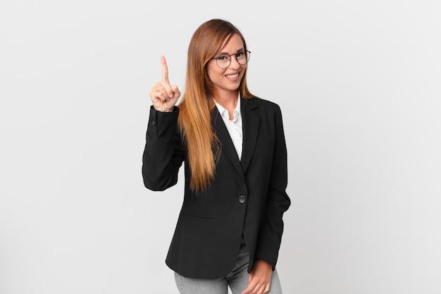 Ładna kobieta uśmiecha się i wygląda przyjaźnie, pokazując numer jeden. pomysł na biznes