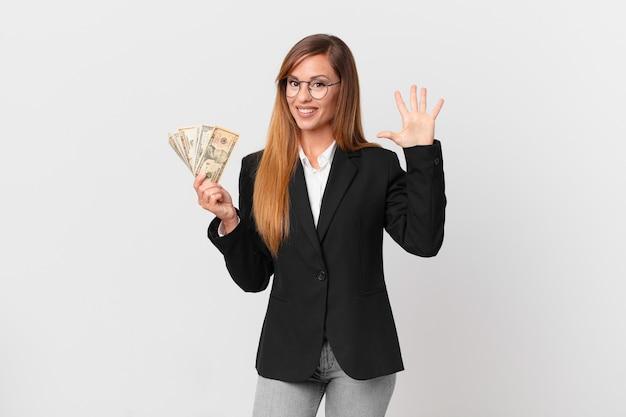 Ładna kobieta uśmiecha się i wygląda przyjaźnie, pokazując numer pięć. koncepcja biznesu i dolarów