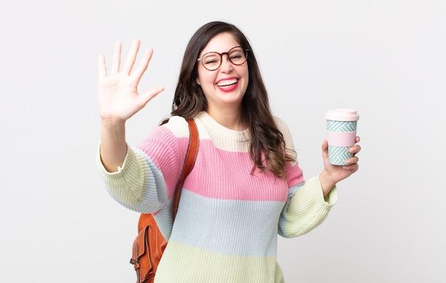 Ładna kobieta uśmiecha się i wygląda przyjaźnie, pokazując numer pięć. koncepcja studenta