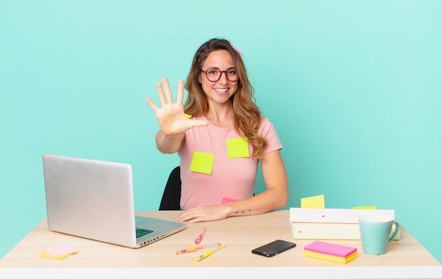 Ładna kobieta uśmiecha się i wygląda przyjaźnie, pokazując numer pięć. koncepcja telepracy