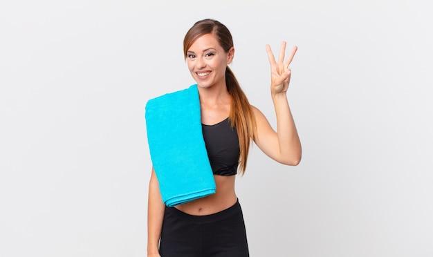 Ładna kobieta uśmiecha się i wygląda przyjaźnie, pokazując numer trzy. koncepcja fitness