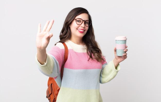 Ładna kobieta uśmiecha się i wygląda przyjaźnie, pokazując numer trzy. koncepcja studenta