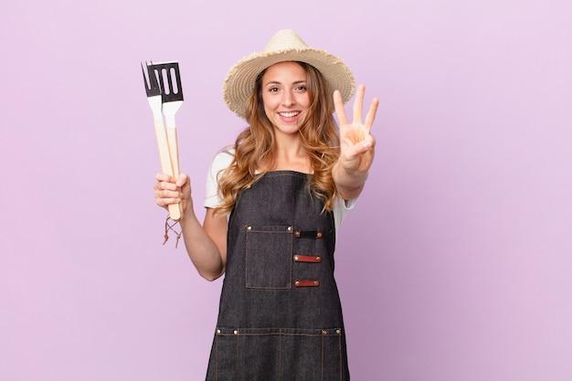 Ładna kobieta uśmiecha się i wygląda przyjaźnie, pokazując numer trzy. koncepcja szefa kuchni z grilla
