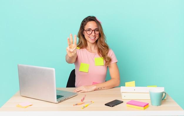 Ładna kobieta uśmiecha się i wygląda przyjaźnie, pokazując numer trzy. koncepcja telepracy