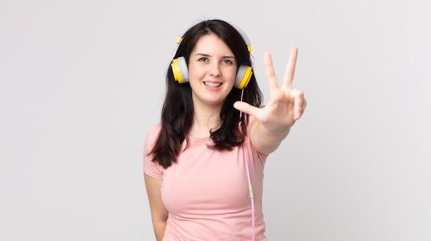 Ładna kobieta uśmiecha się i wygląda przyjaźnie, pokazując numer trzy słuchając muzyki przez słuchawki