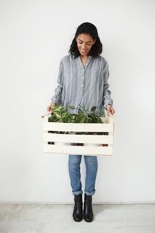 Ładna kobieta uśmiecha się patrząc w dół trzymając pudełko z roślinami w doniczkach na białej ścianie