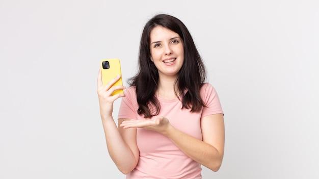 Ładna kobieta uśmiecha się radośnie, czuje się szczęśliwa i pokazuje koncepcję za pomocą smartfona