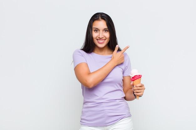 Ładna kobieta uśmiecha się radośnie, czuje się szczęśliwa i wskazuje na bok i do góry, pokazując obiekt w przestrzeni kopii