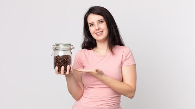 Ładna kobieta uśmiecha się radośnie, czuje się szczęśliwa, pokazuje koncepcję i trzyma butelkę ziaren kawy