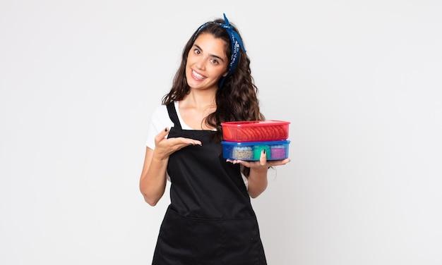 Ładna kobieta uśmiecha się radośnie, czuje się szczęśliwa, pokazuje koncepcję i trzyma tupperware z jedzeniem