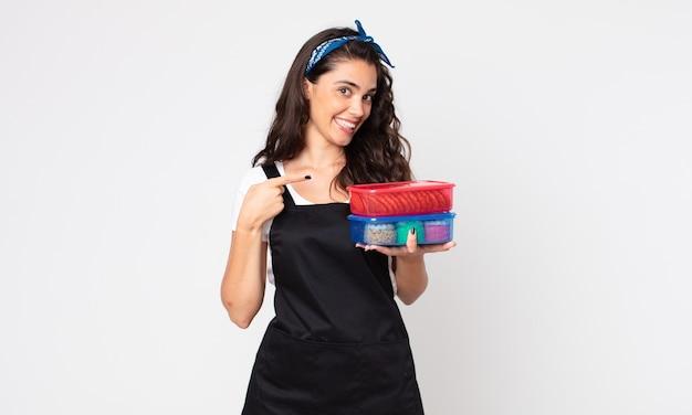 Ładna kobieta uśmiecha się radośnie, czuje się szczęśliwa, wskazuje na bok i trzyma tupperware z jedzeniem