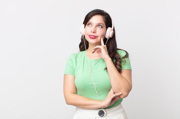 Ładna kobieta uśmiecha się radośnie i marzy lub wątpi w słuchanie muzyki przez słuchawki