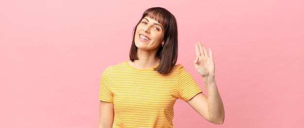 Ładna kobieta uśmiecha się radośnie i radośnie, machając ręką, witając cię i pozdrawiając lub żegnając się