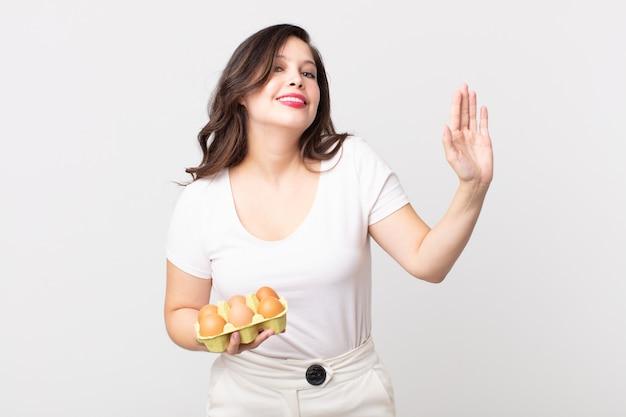 Ładna kobieta uśmiecha się radośnie, macha ręką, wita cię i wita i trzyma pudełko z jajkami