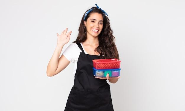Ładna kobieta uśmiecha się radośnie, macha ręką, wita cię i wita i trzyma tupperware z jedzeniem