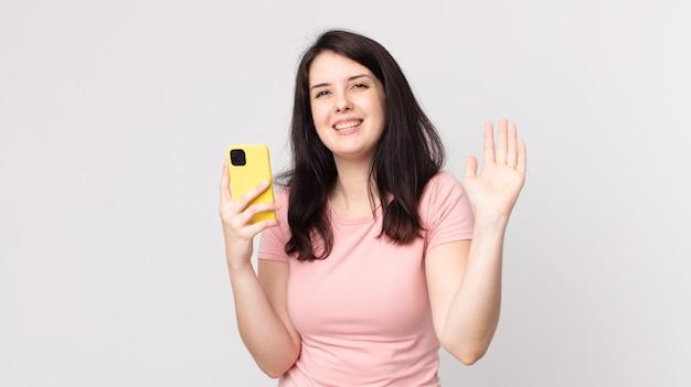 Ładna kobieta uśmiecha się radośnie, macha ręką, wita cię i wita za pomocą smartfona